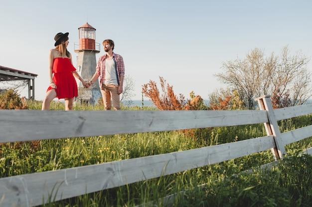 Aantrekkelijke jonge stijlvolle paar verliefd op platteland indie hipster bohemien stijl, weekendvakantie, zomer outfit, rode jurk, groen gras, hand in hand