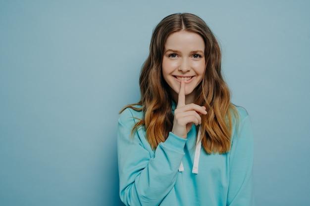 Aantrekkelijke jonge tiener meisje glimlachend terwijl het aanraken van de lippen met de aanwijzer vinger tonen shushing teken dragen casual comfortabele trui poseren geïsoleerd op blauwe studio achtergrond