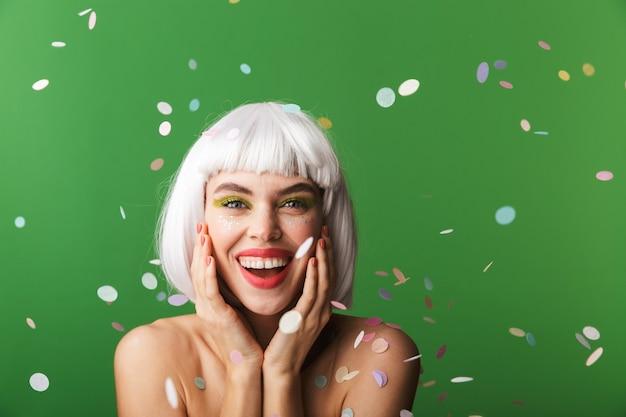 Aantrekkelijke jonge topless vrouw die kort wit haar draagt dat zich onder geïsoleerde confettienregen bevindt