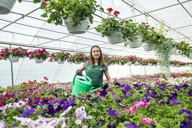 Aantrekkelijke jonge tuinman verzorgt elke dag planten met een gieter in een kas. bezetting in broeikas