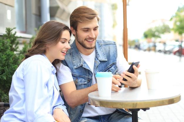 Aantrekkelijke jonge verliefde paar drinken koffie terwijl ze buiten aan de cafétafel zitten, met behulp van mobiele telefoon.