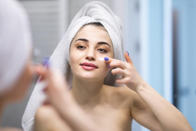 Aantrekkelijke jonge volwassen vrouw brengt gezichtscrème aan, kijk in de spiegel