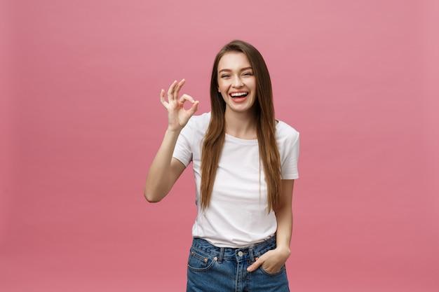Aantrekkelijke jonge volwassen vrouw die ok teken toont