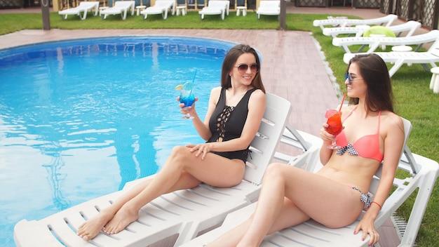 Aantrekkelijke jonge vriendinnen in zwemkleding rusten bij het zwembad met katten in hun handen