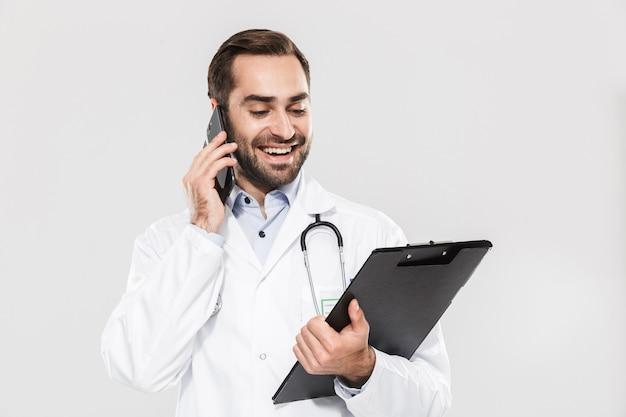 Aantrekkelijke jonge, vrolijke mannelijke arts die unifrom draagt, geïsoleerd over een witte muur staat en aantekeningen maakt tijdens het praten op de mobiele telefoon
