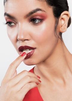 Aantrekkelijke jonge vrouw aan haar lippen te raken