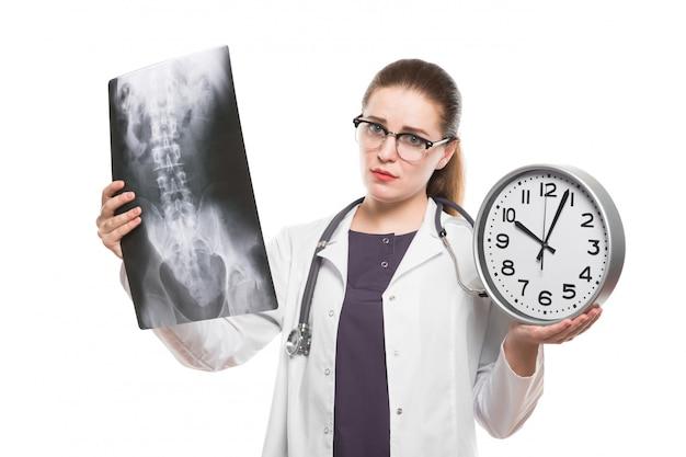 Aantrekkelijke jonge vrouw arts met klok in haar handen met x-ray diagnose in witte uniform