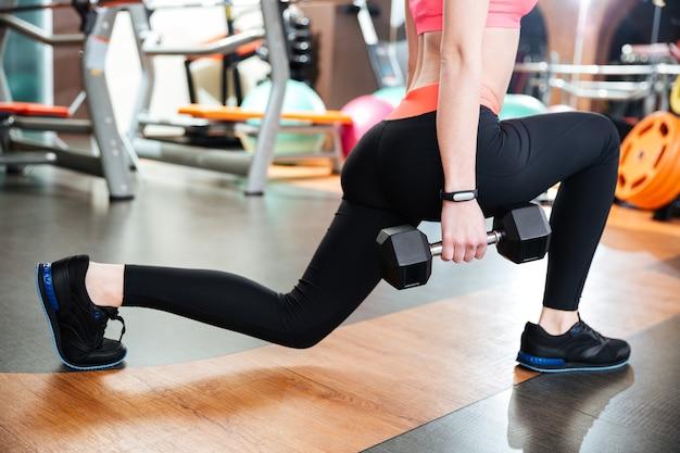 Aantrekkelijke jonge vrouw atleet doet squats met halters in sportschool