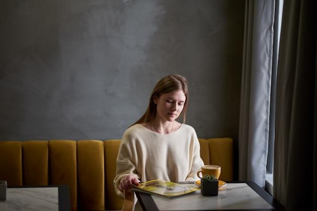 Aantrekkelijke jonge vrouw brengt vrije tijd door in cafés, genietend van de verse koffie en het lezen van een damesblad.