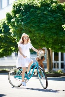 Aantrekkelijke jonge vrouw die berijdend van haar fiets geniet