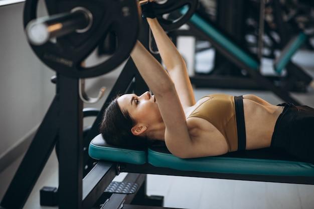 Aantrekkelijke jonge vrouw die bij de gymnastiek uitoefent