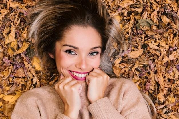 Aantrekkelijke jonge vrouw die bij droge bladeren en het stellen ligt