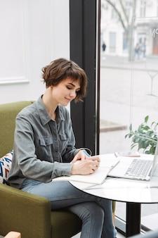 Aantrekkelijke jonge vrouw die binnenshuis aan de cafétafel zit, op een laptop werkt, documenten analyseert