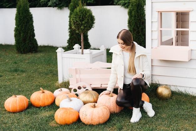 Aantrekkelijke jonge vrouw die buiten haar huis zit met veel halloween-pompoenen