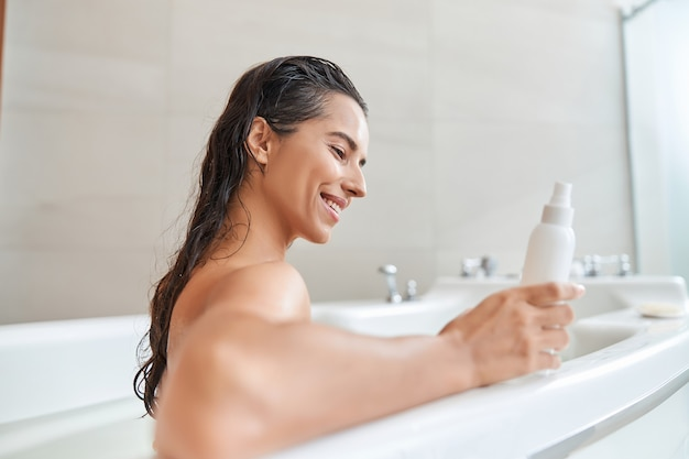 Aantrekkelijke jonge vrouw die een fles lotion vasthoudt terwijl ze ontspant in badkuip