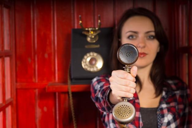 Aantrekkelijke jonge vrouw die een vintage telefoonhoorn naar de kijker reikt vanaf een instrument dat op een houten muur achter haar is gemonteerd