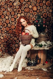 Aantrekkelijke jonge vrouw die een witte wollen sweater en gebreide sokken draagt. kerstmis.