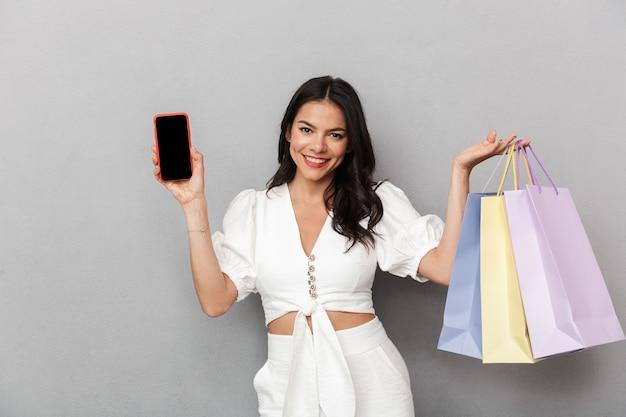 Aantrekkelijke jonge vrouw die een zomeroutfit draagt die geïsoleerd staat over een grijze muur, boodschappentassen draagt, een mobiele telefoon met een leeg scherm vasthoudt