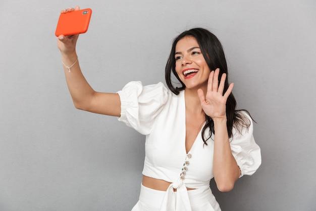 Aantrekkelijke jonge vrouw die een zomeroutfit draagt, geïsoleerd over een grijze muur staat en een selfie maakt