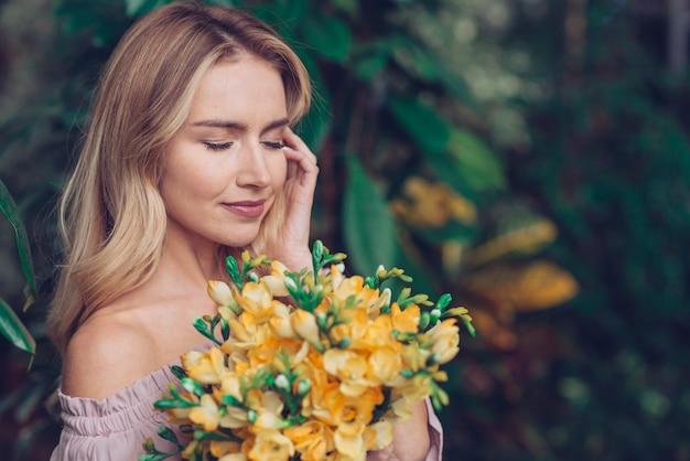 Aantrekkelijke jonge vrouw die gele verse bloemen houdt