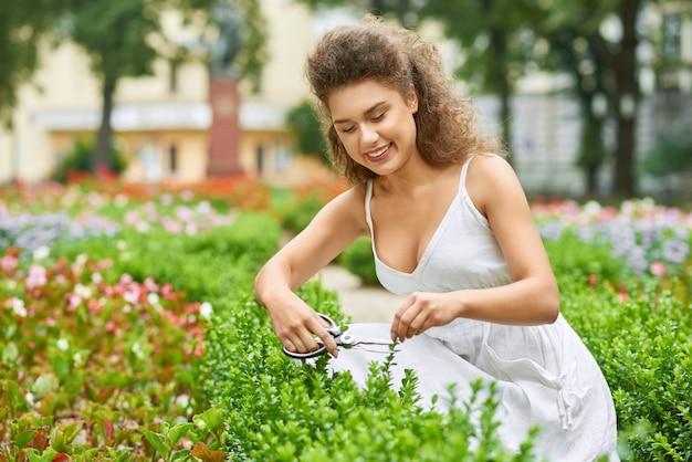 Aantrekkelijke jonge vrouw die gelukkig snijdende in orde makende struiken glimlachen bij haar tuin copyspace werkende tuinman het tuinieren zorghobby het leven levensstijl.