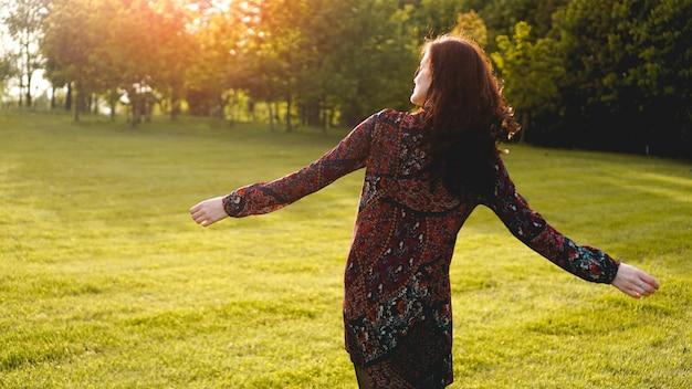 Aantrekkelijke jonge vrouw die geniet van haar tijd buiten in het park - zomertijd