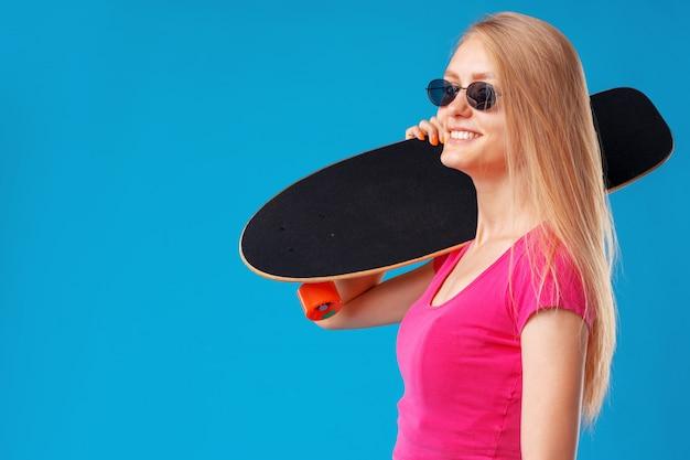 Aantrekkelijke jonge vrouw die haar skateboard over blauw houdt