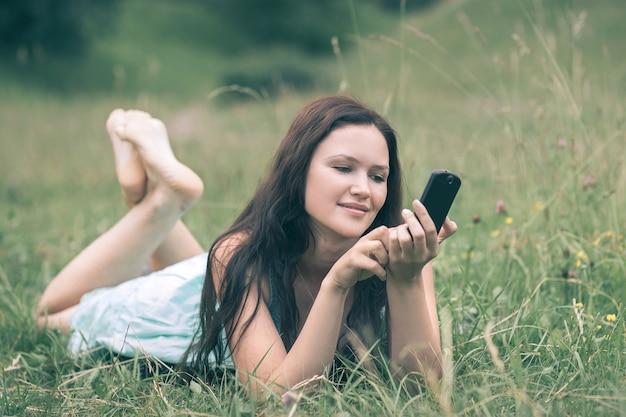 Aantrekkelijke jonge vrouw die haar smartphone gebruikt terwijl ze op een open plek ligt. mensen en technologie