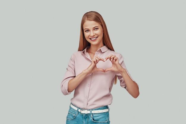 Aantrekkelijke jonge vrouw die hart met handen toont en glimlacht terwijl ze tegen een grijze achtergrond staat
