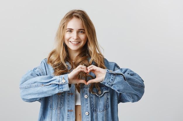 Aantrekkelijke jonge vrouw die hartgebaar toont om als, sympathie of liefde uit te drukken