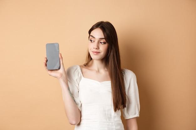 Aantrekkelijke jonge vrouw die het lege smartphonescherm toont, en opzij glimlacht kijkt, die zich op beige achtergrond bevindt.