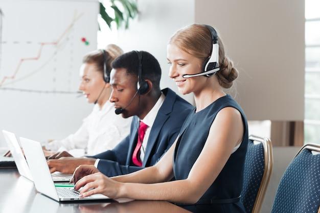 Aantrekkelijke jonge vrouw die in een call centre met zijn collega's werkt
