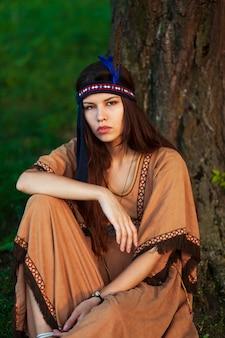 Aantrekkelijke jonge vrouw die in inheemse bohokleding op een gras zitten