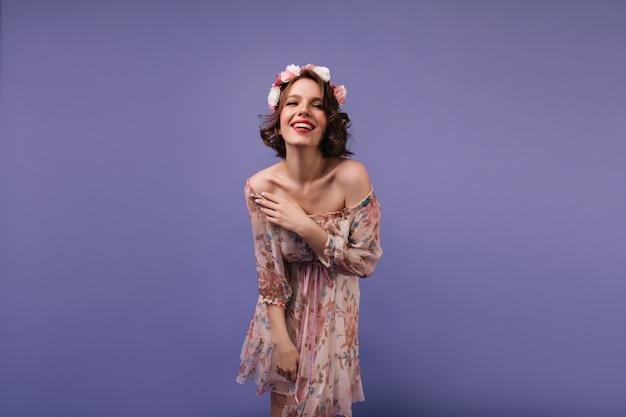 Aantrekkelijke jonge vrouw die in romantische kledij geluk uitdrukt. debonair vrouwelijk model met bloemen op haar hoofd lachend.