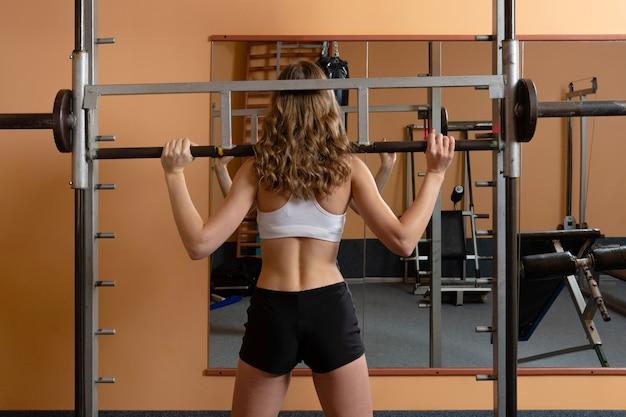 Aantrekkelijke jonge vrouw die in sportslijtage met fitness materiaal in een professionele gymnastiek uitwerkt. training in de sportschool. sport concept.