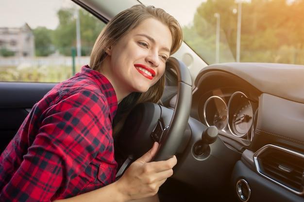 Aantrekkelijke jonge vrouw die in vrijetijdskleding terwijl het drijven van een auto glimlacht