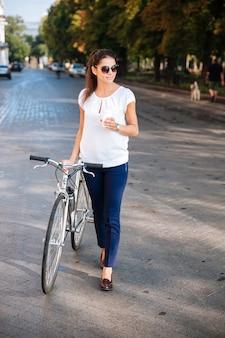 Aantrekkelijke jonge vrouw die in zonnebril met fiets en afhaalkoffie loopt