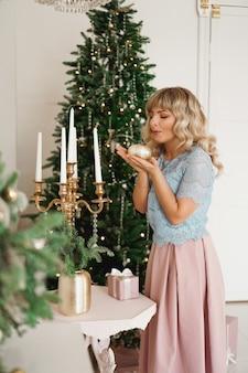 Aantrekkelijke jonge vrouw die lacht terwijl ze een kaars vasthoudt om kerstmis te vieren. nieuwjaar - gezellig interieur