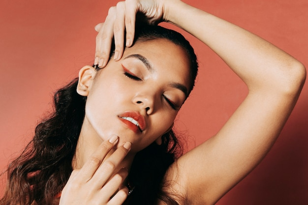 Aantrekkelijke jonge vrouw die met handen rond haar gezicht speelt