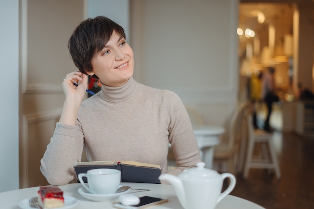 Aantrekkelijke jonge vrouw die met pen in hand op plannen denken en lijst schrijven om in blocnote te doen die van recreatietijd in modieuze koffie genieten