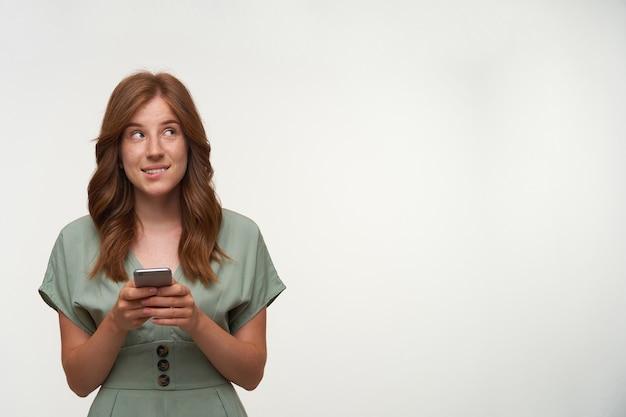 Aantrekkelijke jonge vrouw die met romantisch kapsel dromerig naar boven kijkt, mobiele telefoon in handen houdt en onderlip bijt, positief denkt