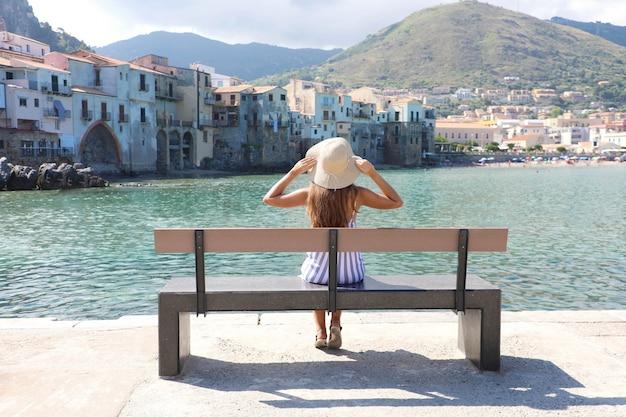 Aantrekkelijke jonge vrouw die met strohoed zittend op een bankje geniet van een uitzicht op het dorp cefalu in italië