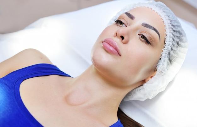 Aantrekkelijke jonge vrouw die op bed of laag in schoonheidssalon of schoonheidskliniek liggen.