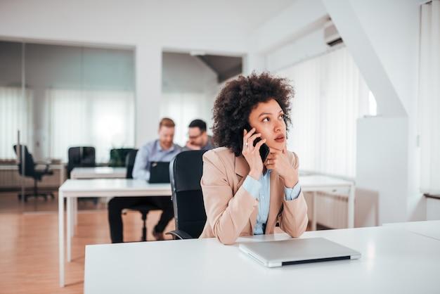 Aantrekkelijke jonge vrouw die op de mobiele telefoon spreekt terwijl het zitten op haar werkende plaats in bureau.