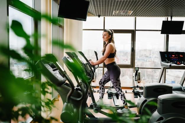 Aantrekkelijke jonge vrouw die op een elliptische crosstrainer in sportclub uitoefent.