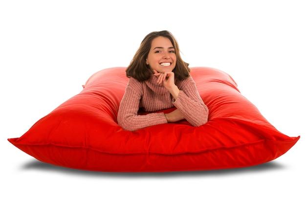 Aantrekkelijke jonge vrouw die op rood vierkant gevormde zitzakbank voor woonkamer of andere ruimte ligt die op wit wordt geïsoleerd