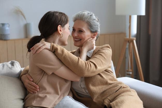 Aantrekkelijke jonge vrouw die rijpe moeder omhelst, liefdevol glimlacht.