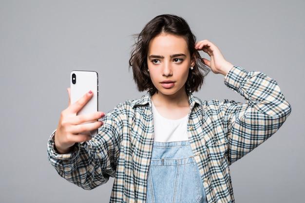Aantrekkelijke jonge vrouw die selfie met telefoon neemt