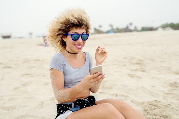Aantrekkelijke jonge vrouw die selfies neemt bij het strand. zomerstemming.