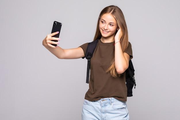 Aantrekkelijke jonge vrouw die selfies op de camera van de mobiele telefoon op witte muur maakt